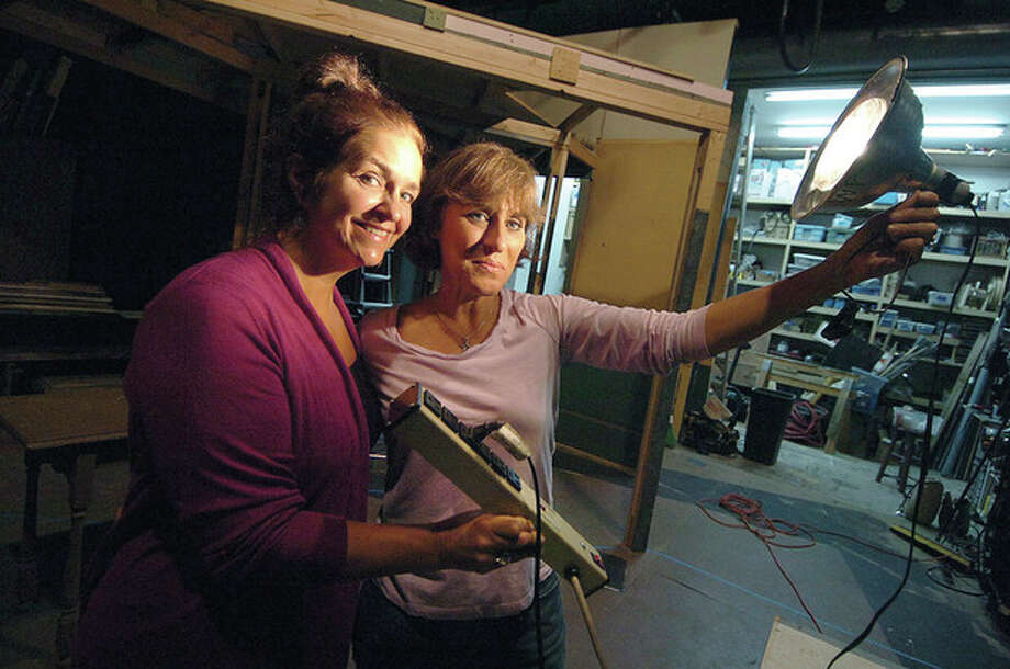 Photo by Alex von Kleydorff. Wilton Playshop board members, from left, Donna Savage and Meg Fuentes use a painter's light to illuminate the lighting problem at the Playshop. / 2011 The Hour Newspapers/ Alex von Kleydorff