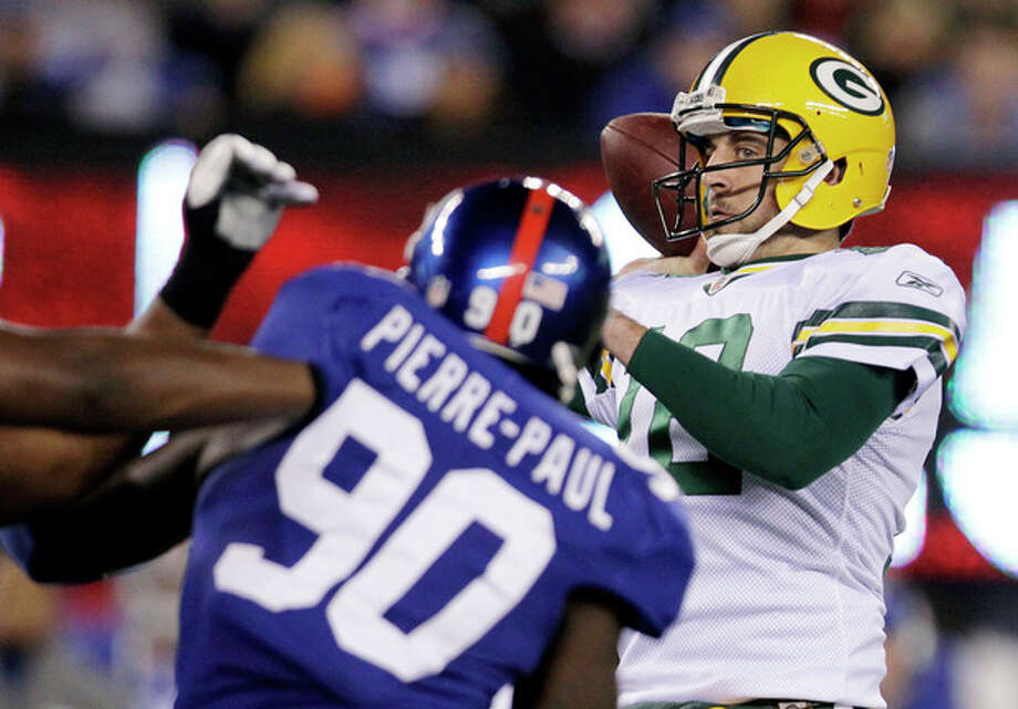 Green Bay Packers quarterback Aaron Rodgers (12) throws a pass as New York Giants defensive end Jason Pierre-Paul (90) rushes during the third quarter of an NFL football game Sunday, Dec. 4, 2011, in East Rutherford, N.J. (AP Photo/Julio Cortez) / AP