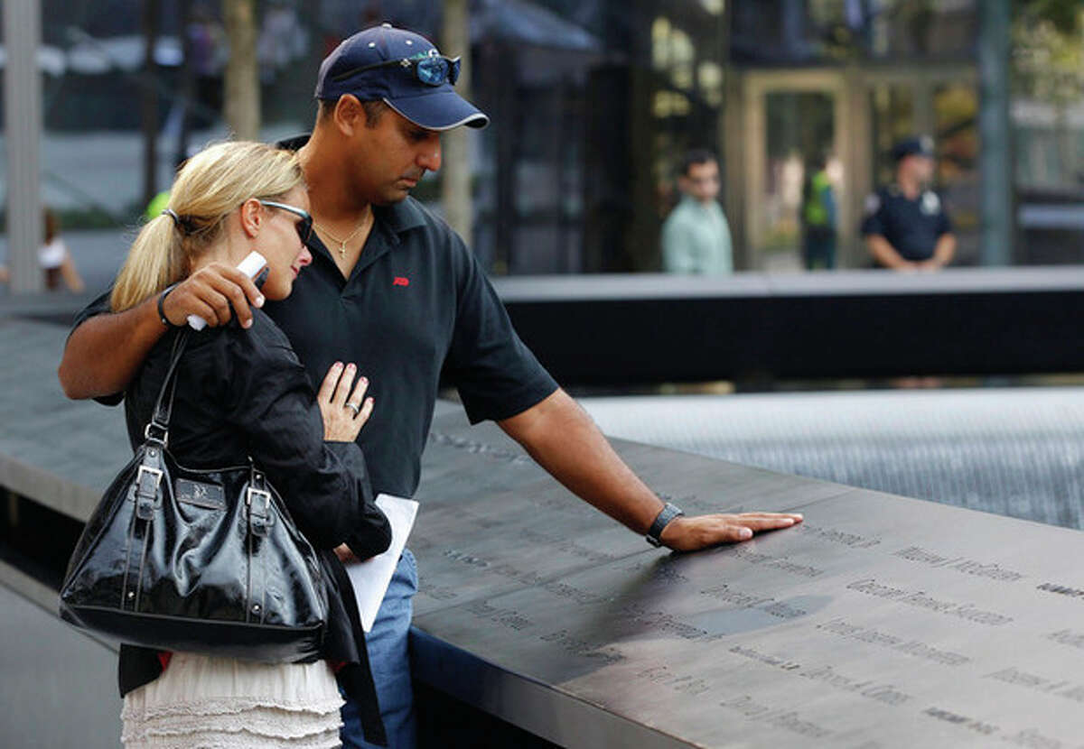 AP photo / Mike Segar, Pool Shauna Camp and Anthony Camp, who lost their uncle, Faustino Apostol Jr., in the 9/11 terrorist attacks, look at the panel inscribed with his name during the first day that the 911 memorial plaza was opened to the public at the World Trade Center site in New York.