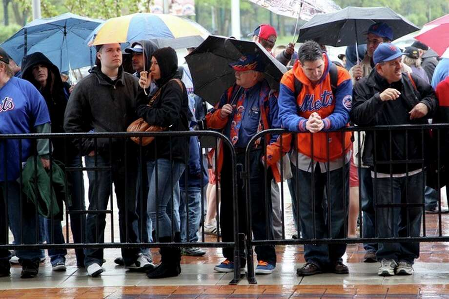 Fans stand in the rain while looking through the gates into Citi Field after the baseball game between the New York Mets and San Francisco Giants was postponed due to weather, Sunday, April 22, 2012, in New York. A spring nor'easter along the East Coast is expected to bring rain and heavy winds and even snow in some places as it strengthens into early Monday, a punctuation to a relatively dry stretch of weather for the Northeast. (AP Photo/Seth Wenig) / AP