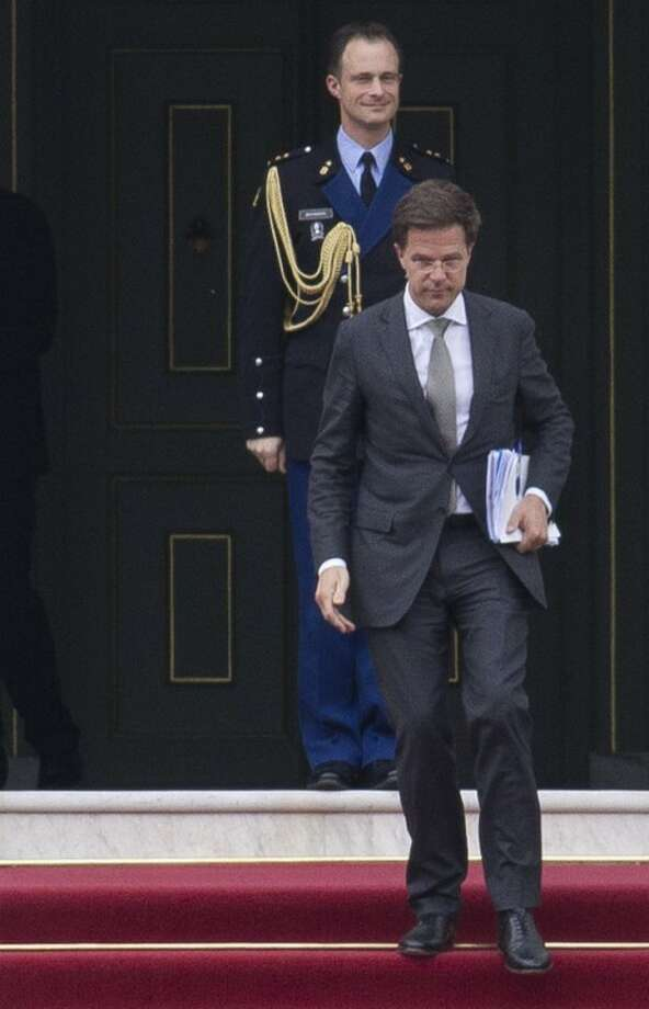 Dutch prime minister Mark Rutte, foreground, leaves royal palace Huis ten Bosch after meeting with Dutch Queen Beatrix in The Hague, Netherlands, Monday April 23, 2012. Rutte was reported to have handed in his resignation to the Queen after seven weeks of talks to hammer out an austerity package aimed at bringing the Dutch budget deficit back within European Union limits collapsed Saturday. (AP Photo/Peter Dejong)