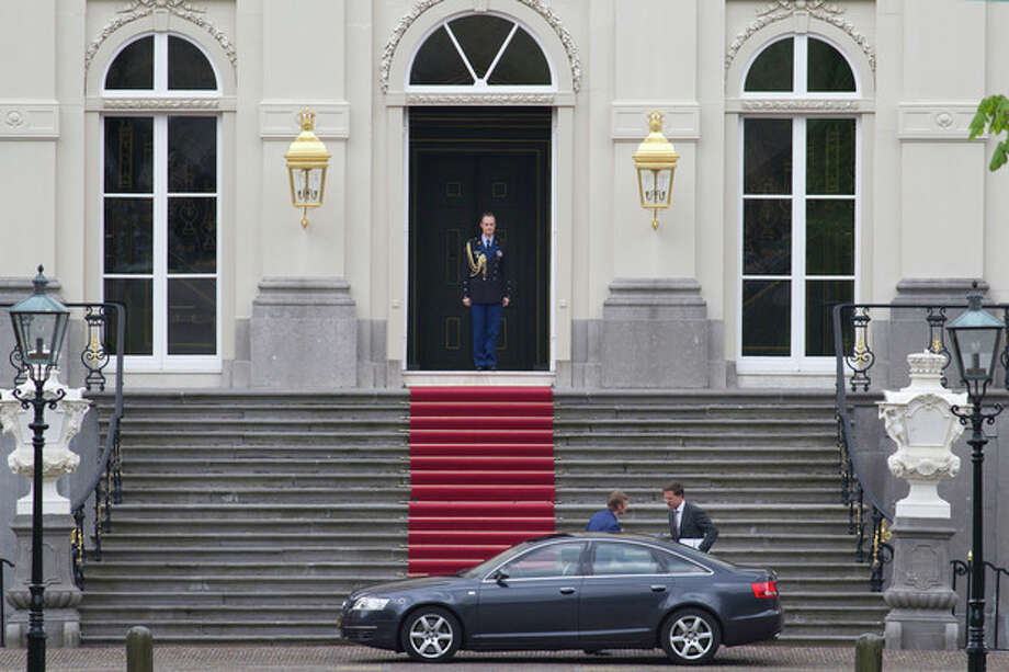 Dutch prime minister Mark Rutte, bottom right, gets into his car as he leaves royal palace Huis ten Bosch after meeting with Dutch Queen Beatrix in The Hague, Netherlands, Monday April 23, 2012. Rutte is reported to have handed in his resignation to the Queen after seven weeks of talks to hammer out an austerity package aimed at bringing the Dutch budget deficit back within European Union limits collapsed Saturday. (AP Photo/Peter Dejong) / AP