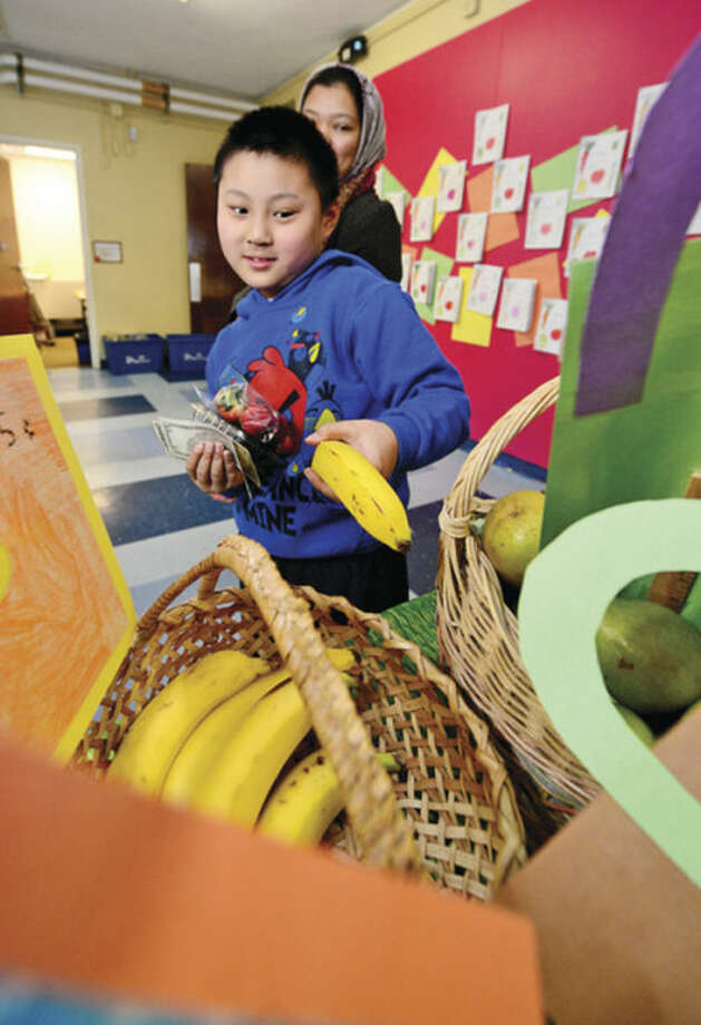 Columbus Magnet School 5th grader Christopher Gong picks out a banana during the school's annual Big Bag Market where the first grade learns basic business skills Wednesday. The market continues Thursday and Friday 9am to 11.Hour photo / Erik Trautmann