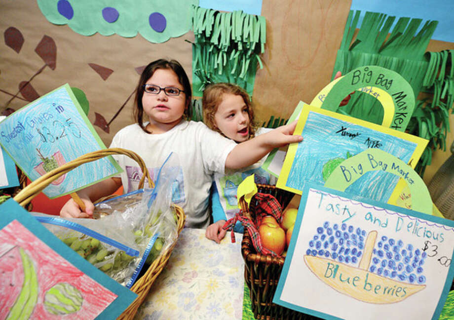 Columbus Magnet School first graders Ietzy Zuniga and Seve Zurkowski participate in the school's annual Big Bag Market where the first grade learns business skills Wednesday. The market continues Thursday and Friday 9am to 11.Hour photo / Erik Trautmann / (C)2012, The Hour Newspapers, all rights reserved