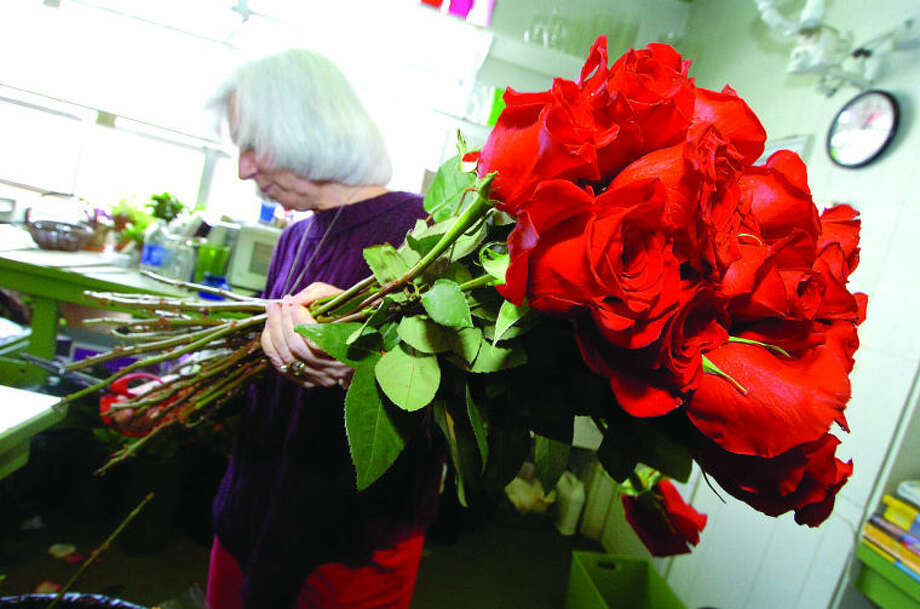 Nita Alarcon makes sure the thorns are removed and the ends of the stems are fresh cut on Long Stem Red Roses at Stewart Flowers in Wilton Center on Tuesday. Valentines day is Thursday and its by far the busiest day for Florists next to Mothers Day