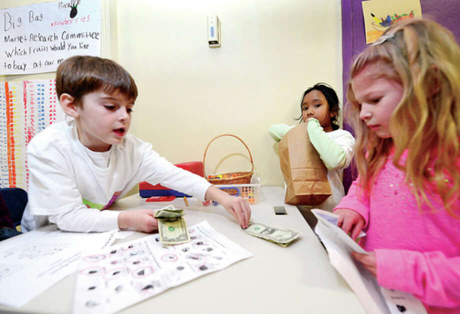 Columbus Magnet School first grader Noah Wasserman counts out change for kindergartner Emma Mueller as Raisa Yousu bgas the prduce during the school's annual Big Bag Market where first graders learn business skills Wednesday. The market continues Thursday and Friday 9am to 11.Hour photo / Erik Trautmann / (C)2012, The Hour Newspapers, all rights reserved