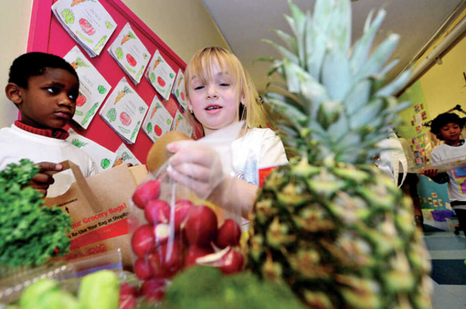 Columbus Magnet School first grader Ella Schweizer checks out her produce while Thomas Frank waits to bag her groceries during the school's annual Big Bag Market where first graders learn basic business skills Wednesday. The market continues Thursday and Friday 9am to 11.Hour photo / Erik Trautmann / (C)2012, The Hour Newspapers, all rights reserved