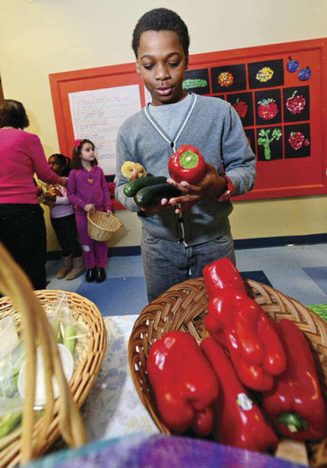 Columbus Magnet School 5th grader Luca Napoli-Bulteryst picks out produce during the school's annual Big Bag Market where the first grade learns basic business skills Wednesday. The market continues Thursday and Friday 9am to 11.Hour photo / Erik Trautmann