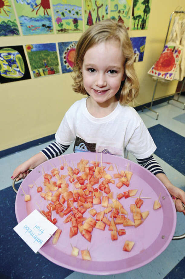 Columbus Magnet School first grader Mary Kate Hopkins serves up grapefruit during the school's annul Big Bag Market where first graders learn business skills Wednesday. The market continues Thursday and Friday 9am to 11.Hour photo / Erik Trautmann