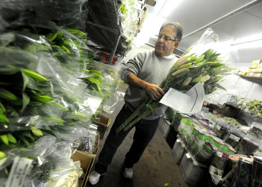 Stamford Steve Geruso, owner of East Coast Wholesale Florist in Norwalk, keeps the stock sheves full on the Sunday before Valentine's Day in this file photo.