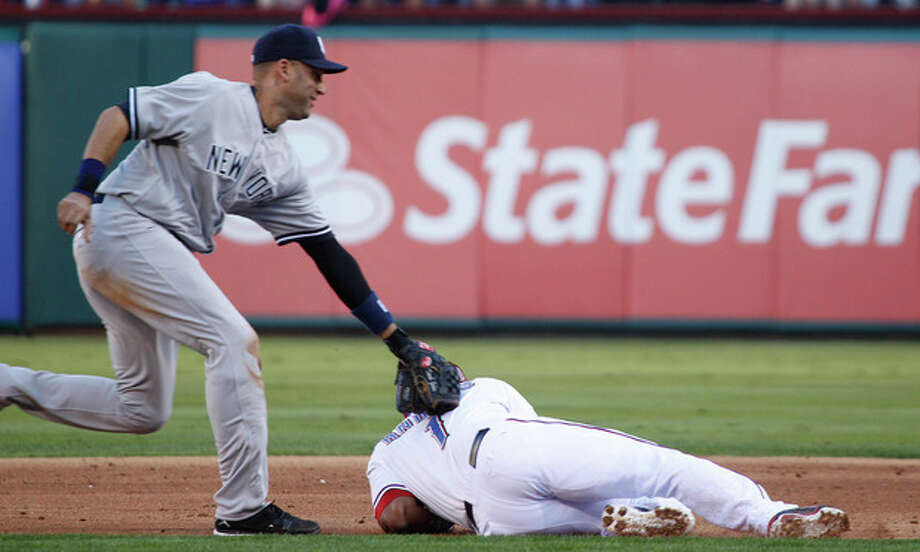 New York Yankees shortstop Derek Jeter tags out Texas Rangers' Elvis Andrus after Andrus was caught between first and second base during the first inning of a baseball game, Monday, April 23, 2012, in Arlington, Texas. (AP Photo/LM Otero) / AP