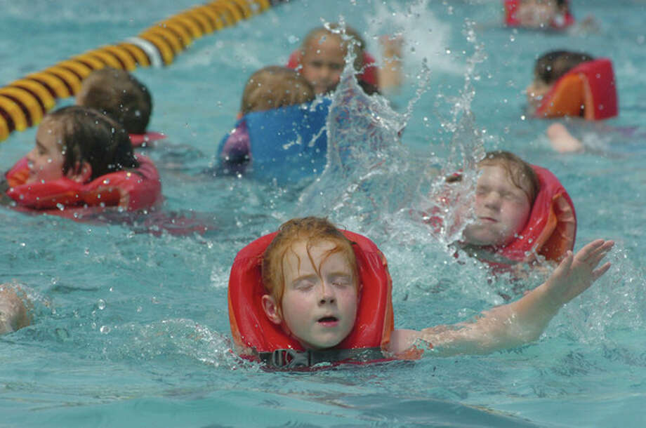 Hour Photo/Alex von Kleydorff. 5yr old Emma Love along with other 1st graders swim the breaststroke during an instruction swimming session at Camp Gordyland summer day camp at The Wilton Family Y / 2011 The Hour Newspapers