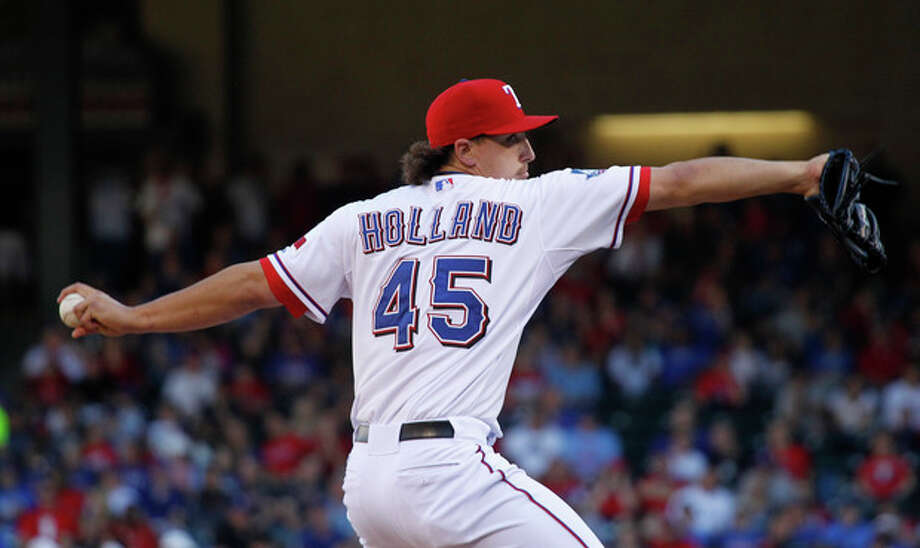 Texas Rangers starting pitcher Derek Holland throws during the first inning of a baseball game against the New York Yankees, Monday, April 23, 2012, in Arlington, Texas. (AP Photo/LM Otero) / AP