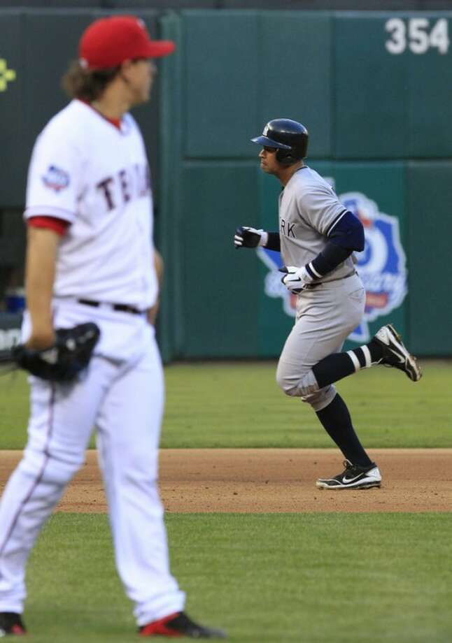 New York Yankees Alex Rodriguez, right, rounds the bases after his three-run home run as Texas Rangers starting pitcher Derek Holland waits during the fifth inning of a baseball game Monday, April 23, 2012, in Arlington, Texas. (AP Photo/LM Otero)