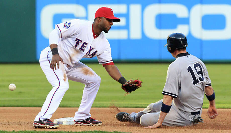 Texas Rangers shortstop Elvis Andrus can't place the tag with the ball as New York Yankees Chris Stewart (19) slides into second base during the fourth inning of a baseball game Monday, April 23, 2012, in Arlington, Texas. Stewart advanced from first on a missed pick-off throw from pitcher Derek Holland. (AP Photo/LM Otero) / AP