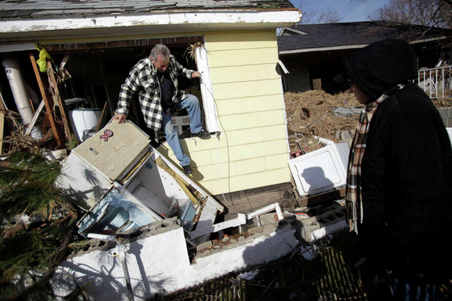 FILE - In a Tuesday, Nov. 20, 2012 file photo, Joe Vanvaketis climbs out of his home, which was severely damaged by Superstorm Sandy, after trying to recover some personal items while his wife Inez Vanvaketis watches in the Oakwood Beach section of Staten Island, New York. The National Hurricane Center released a report Tuesday, Feb. 12, 2013 that says says Superstorm Sandy was the deadliest hurricane to hit the northeastern U.S. in 40 years and the second-costliest in the nation's history. The report attributes 72 deaths in the U.S. directly to Sandy, from Maryland to New Hampshire. That's more than any hurricane to hit the northeastern U.S. since Hurricane Agnes killed 122 people in 1972. (AP Photo/Seth Wenig, File) / AP