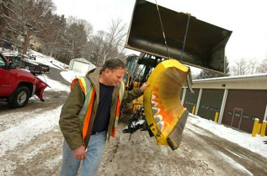 Photo/Alex von Kleydorff. Wilton DPW Highway Supervisor Bob Flemming steadies a plow blade as Sr Mechanic Christopher Litwin uses a loader to move the plow into the town garage for repair of a leveling piston that broke while plowing Wilton''s roads.