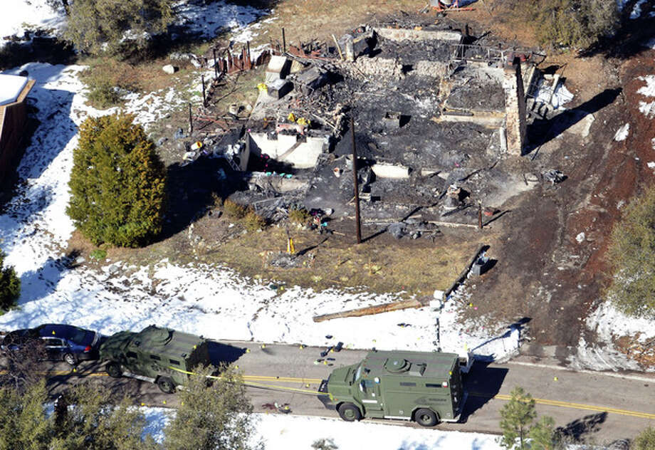 In this aerial photo, law enforcement authorities investigate the burn-out cabin Wednesday, Feb.13, 2013 where accused quadruple-murder suspect Christopher Dorner was believed to have died after barricading himself inside, during a Tuesday stand-off with police in the Angeles Oaks area of Big Bear, Calif. San Bernardino Sheriff's Deputy Jeremiah MacKay was killed and another wounded during the shootout with Dorner. (AP Photo/The Sun, John Valenzuela) / San Bernardino Sun