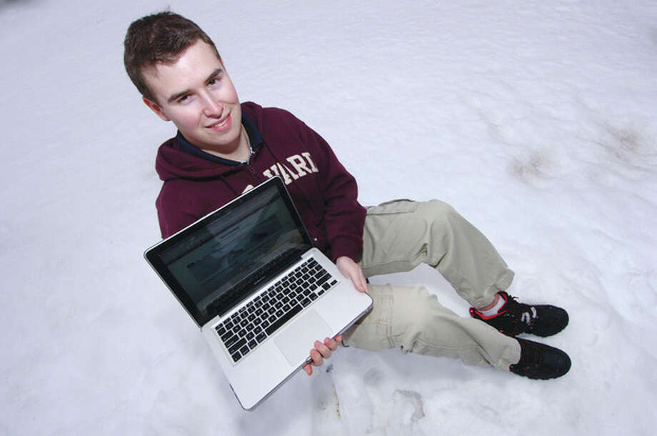 Hour Photo/ Alex von KleydorffWeatherman Jacob Meisel sits in a snow bank after predicting accurately the snowfall totals from this past weekend on his swctweather.com weather site. / 2013 The Hour Newspapers