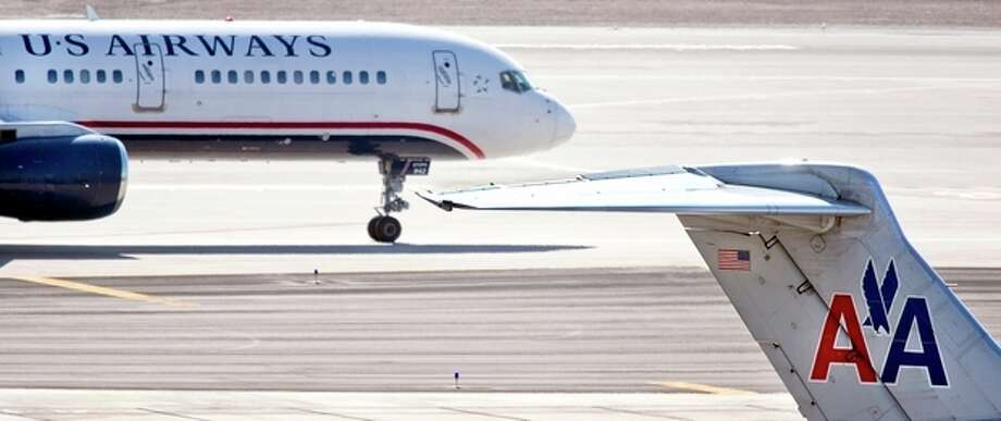 FILE - In this Feb. 7, 2013 file photo, a US Airways jet taxis past an American Airlines jet parked at the gate at Sky Harbor International Airport in Phoenix. The merger of US Airways and American Airlines has given birth to a mega airline with more passengers than any other in the world. (AP Photo/The Arizona Republic,Tom Tinkle, File) MARICOPA COUNTY OUT; MAGS OUT; / The Arizona Republic