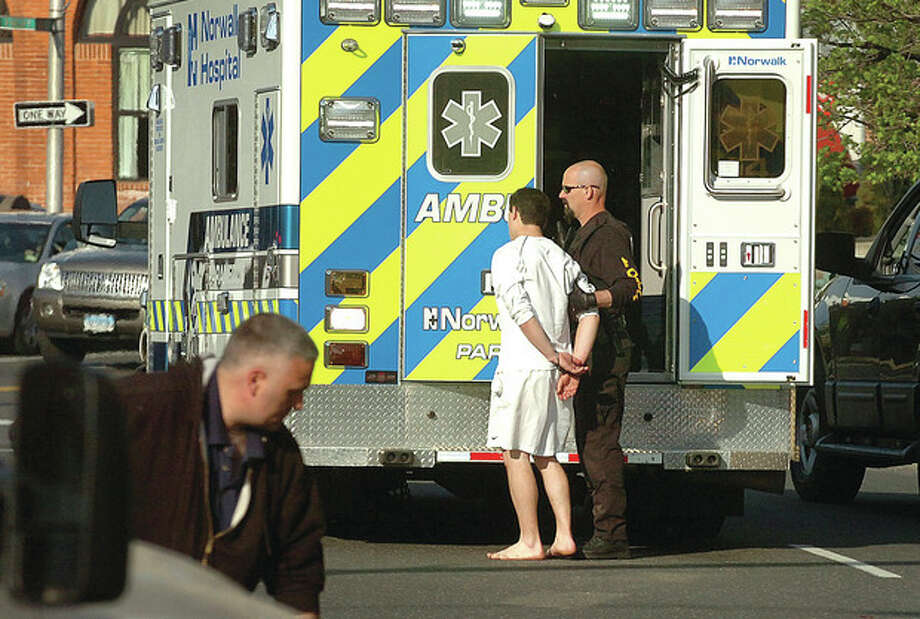 Hour Photo/ Alex von Kleydorff. A person in Handcuffs is led to an ambulance on Wall st. / The Hour Newspapers