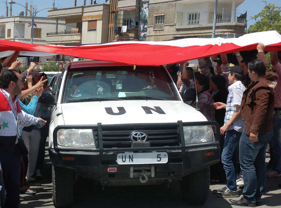 In this photo released by the Syrian official news agency SANA, a UN observers vehicle passes under a huge Syrian flag held by Syrian President Bashar Assad supporters during their visit to the pro-Syrian regime neighborhoods, in Homs province, central Syria, on Monday April 23, 2012. United Nations observers monitoring Syria's shaky cease-fire visited a string of rebellious Damascus suburbs Monday, while the European Union looked set to levy new sanctions to increase the pressure on President Bashar Assad's regime. (AP Photo/SANA) / SANA