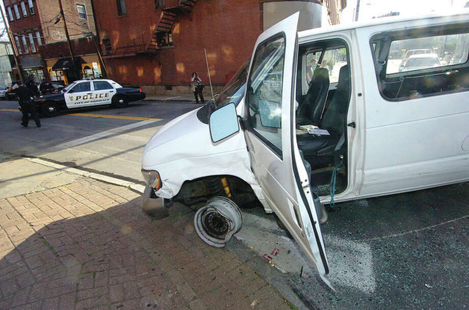 Hour photo / Alex von KleydorffA white van sits partially on a sidewalk after being involved in a multi-vehicle accident Thursday on Wall Street in Norwalk. / The Hour Newspapers