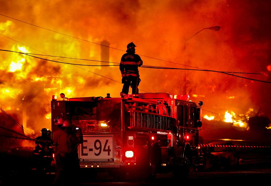 A Daly City firefighter stands atop an engine to survey the fire on Claremont Drive in San Bruno, where a suspected explosion in a gas line ignited the area. PG&E is set to go to trial in federal court in San Francisco on various charges related to the deadly blast. Photo: Brant Ward, The San Francisco Chronicle