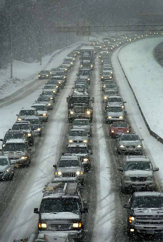 Snow accumulations surprised commuters Tuesday morning causing delays on 1-95 Southbound. Hour photo / Erik Trautmann