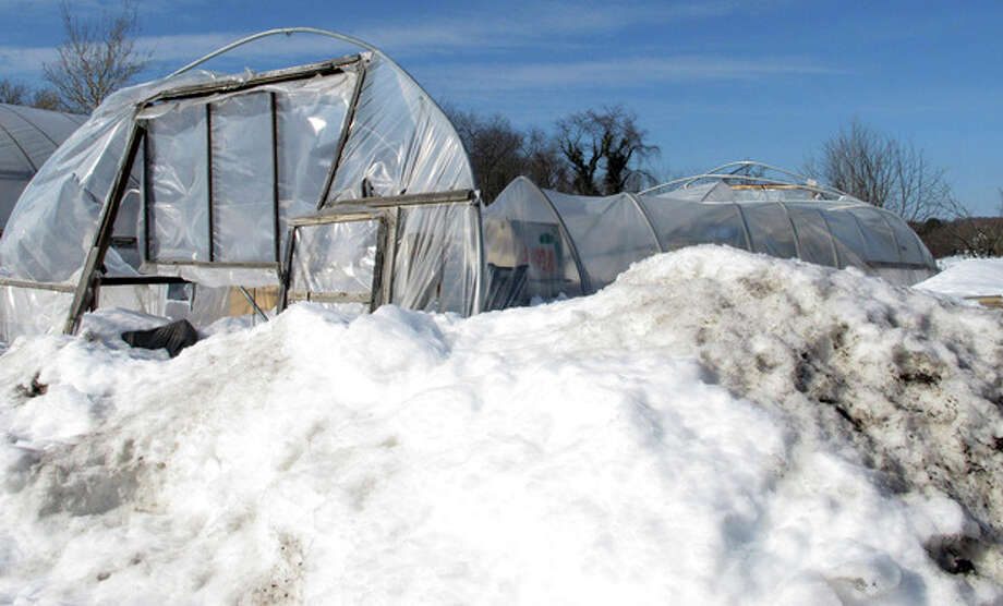A collapsed greenhouse sits surrounded by snow Wednesday, Feb. 13, 2013, at Sunny Border Nurseries in the Kensington section of Berlin, Conn. Five of the nursery's 16 greenhouses caved in after the heavy snowfall Friday and Saturday. Much of the damage in Connecticut was to the state's nursery and landscaping businesses, which account for more than $1 billion sales, or about half of all agriculture in Connecticut. (AP Photo/Dave Collins) / AP