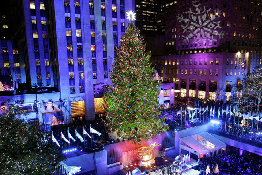 """FILE - In this Wednesday, Nov. 28, 2012 file photo, the Rockefeller Center Christmas tree is lit during the 80th annual tree lighting ceremony at Rockefeller Center in New York. Comcast said Tuesday, Feb. 12, 2013, that it's buying General Electric's 49 percent stake in the NBCUniversal joint venture for $16.7 billion several years early, as the company takes advantage of low borrowing costs and what CEO Brian Roberts called a """"very attractive price.""""(AP Photo/Kathy Willens) / AP"""