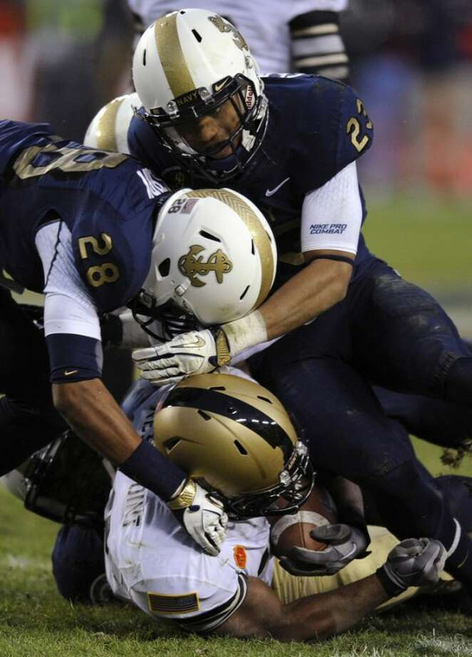 Navy defenders David Sperry (28) and Eric Graham (23) tackle Army running back Larry Dixon in the second half of an NCAA college football game in Landover, Md., Saturday, Dec. 10, 2011. (AP Photo/Nick Wass)