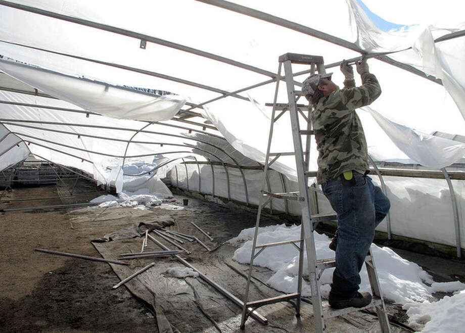 Orlando Nunez dismantles a greenhouse that collapsed under the weight of snow at Sunny Border Nurseries in the Kensington section of Berlin, Conn., Wednesday, Feb. 13, 2013. Five of the nursery's 16 greenhouses caved in after the heavy snowfall Friday and Saturday. Much of the damage in Connecticut was to the state's nursery and landscaping businesses, which account for more than $1 billion sales, or about half of all agriculture in Connecticut. (AP Photo/Dave Collins) / AP