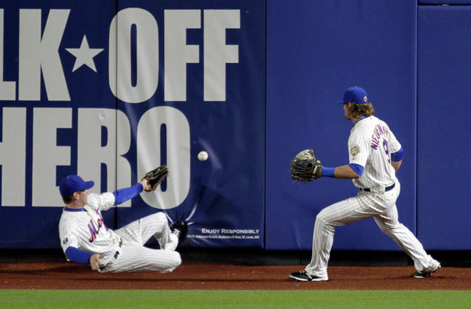 New York Mets' Jason Bay, left, and Kirk Nieuwenhuis try to field a triple by San Francisco Giants' Nate Schierholtz during the first inning of the second baseball game of a doubleheader, Monday, April 23, 2012, in New York. (AP Photo/Seth Wenig) / AP