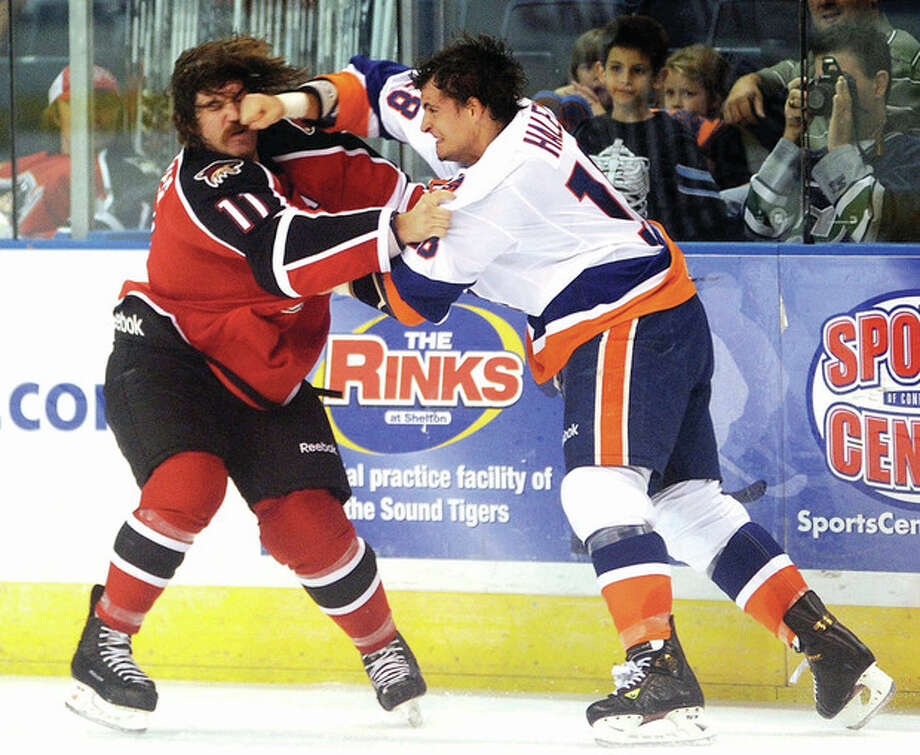 Hour photo/John Nash Michael Haley of the Bridgeport Sound Tigers lands a punch as he scuffles with the Portland Pirates' Ryan Hollweg during Saturday night's AHL esason opener in Bridgeport.