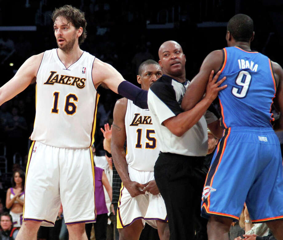 Los Angeles Lakers' Pau Gasol (16), of Spain, stands between an official and Oklahoma City Thunder player after Lakers' Metta World Peace (15) was called for a double flagrant foul and ejected from the game in the first half of an NBA basketball game, Sunday, April 22, 2012, in Los Angeles. (AP Photo/Reed Saxon) / AP