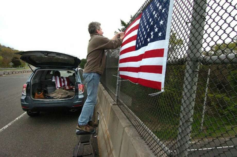 Photo/Alex von Kleydorff. Chris McCormick fastens an American flag into the fence along the southbound Sherwood Island Connector over Interstate 95 in Westport. News of Bin Ladens death promted him and others to place the flags along I95 and the Merritt Parkway on Monday.