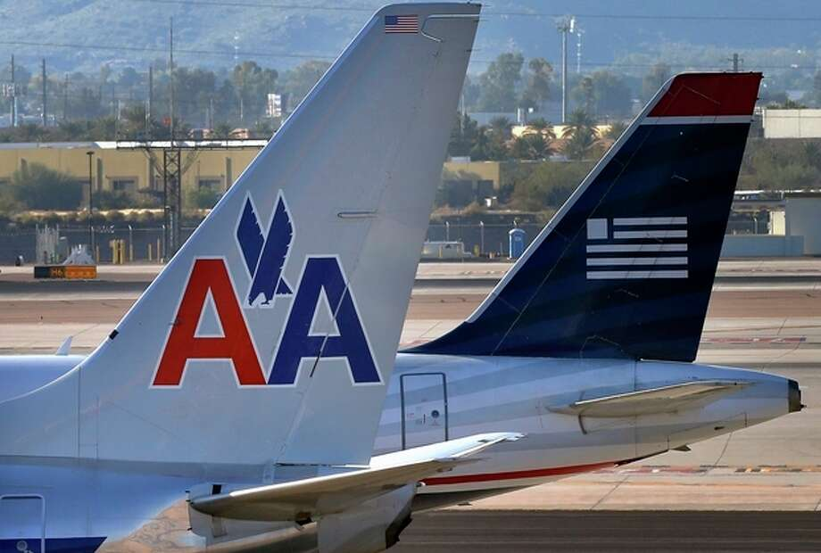 A U.S. Airways jet passes an American Airlines jet, Thursday, Feb. 14, 2013 at Sky Harbor International Airport in Phoenix. The merger of the two airlines has given birth to a mega airline with more passengers than any other in the world. (AP Photo/Matt York) / AP