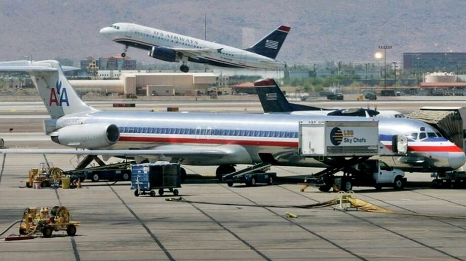 FILE - In this June 23, 2008 file photo, a US Airways jet takes off as an American Airlines jet is prepped for takeoff at Sky Harbor International Airport in Phoenix. The merger of US Airways and American Airlines has given birth to a mega airline with more passengers than any other in the world. (AP Photo/Matt York, File) / AP