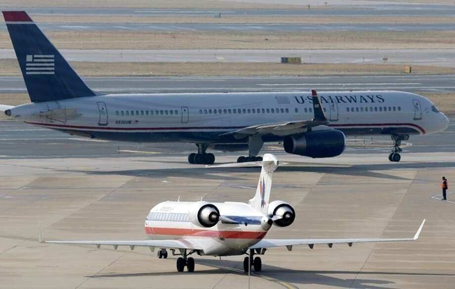 An American Airlines jet taxis near a US Airways jet at the Philadelphia International Airport, Thursday, Feb. 14, 2013, in Philadelphia. The merger of US Airways and American Airlines has given birth to a mega airline with more passengers than any other in the world. (AP Photo/Matt Rourke) / AP