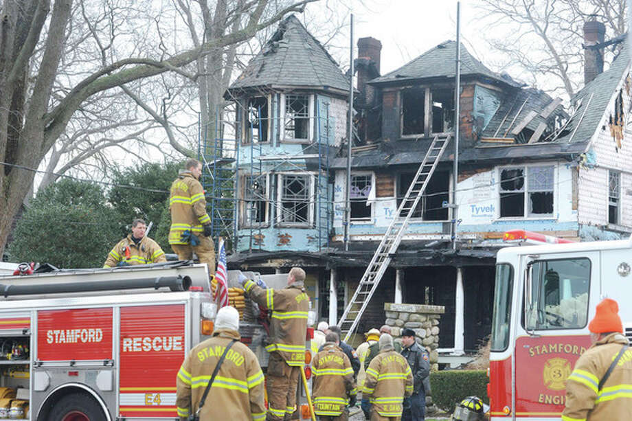 Hour photo / Matthew Vinci Stamford fire and rescue teams work outside of a home at 2267 Shippan Ave. in Stamford after a fire broke out at 5 a.m. Christmas morning, killing five occupants. / (C)2011, The Hour Newspapers, all rights reserved
