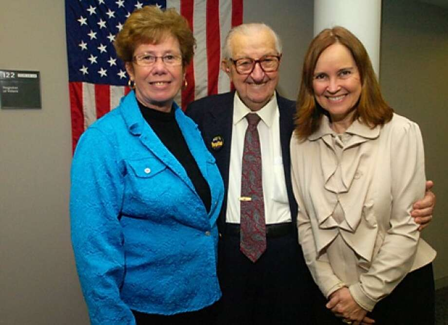 Bill Harrick, the oldest city poll worker, celebrated his 100th birthday Wednesday with Republican Registrar of Voters, Karen Doyle Lyons, and the Secretary of State, Denise Merrill. Hour photo / Erik Trautmann