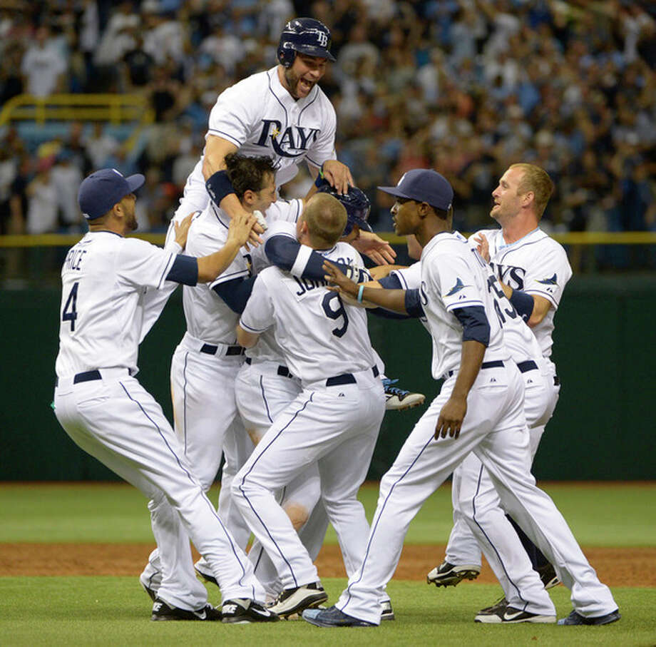 Tampa Bay Rays' Carlos Pena, center (obscured), is swarmed by teammates after hitting the game-winning RBI single in the ninth inning for a 7-6 win over the New York Yankees in a baseball game in St. Petersburg, Fla., Friday, April 6, 2012.(AP Photo/Phelan M. Ebenhack) / FR121174 AP