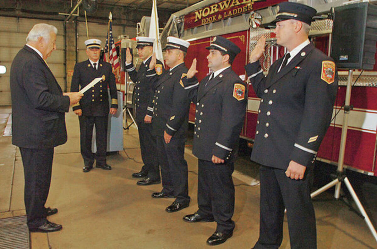 Hour photo / Erik Trautmann Norwalk Fire Department Capt. Adam Markowitz, Capt. Mark Franzen, Lt. Nick Giancasporo and Lt. Scott Rywolt received their official swearing-in for their new promotion from Mayor Richard A. Moccia, while Fire Chief Denis McCarthy looks on Tuesday afternoon.