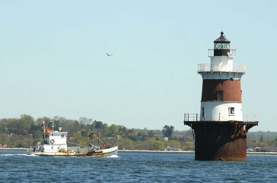 Photo by CHRIS BOSAK An oyster boat cruises in Long Island Sound near Peck's Ledge Light House off the coast of Norwalk this week.