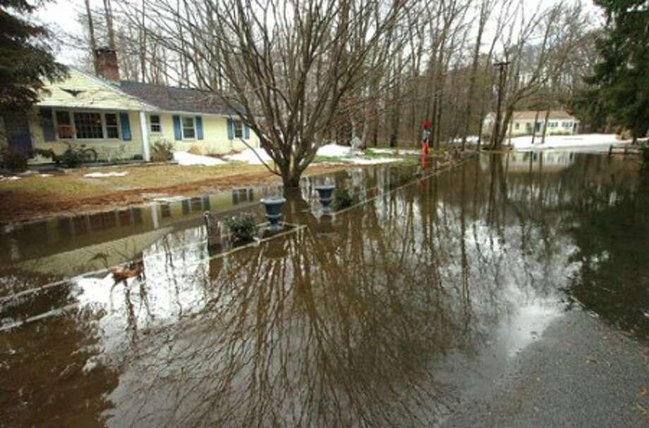Photo/Alex von Kleydorff. Arrowhead Rd is underwater in Wilton Monday morning as the Norwalk River overflows