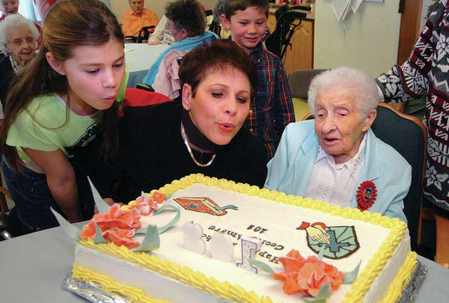 Hour Photo/Alex von Kleydorff. Sister Mary Cecile Amore SSND celebrates 108 years with a cake and Neice Cecile Rodia and Great Grand Neice Gia and Great Grand Nephew Lex to help blow out the candles at Lourdes Health Care Center at School Sisters of Notre Dame in Wilton / 2013 The Hour Newspapers