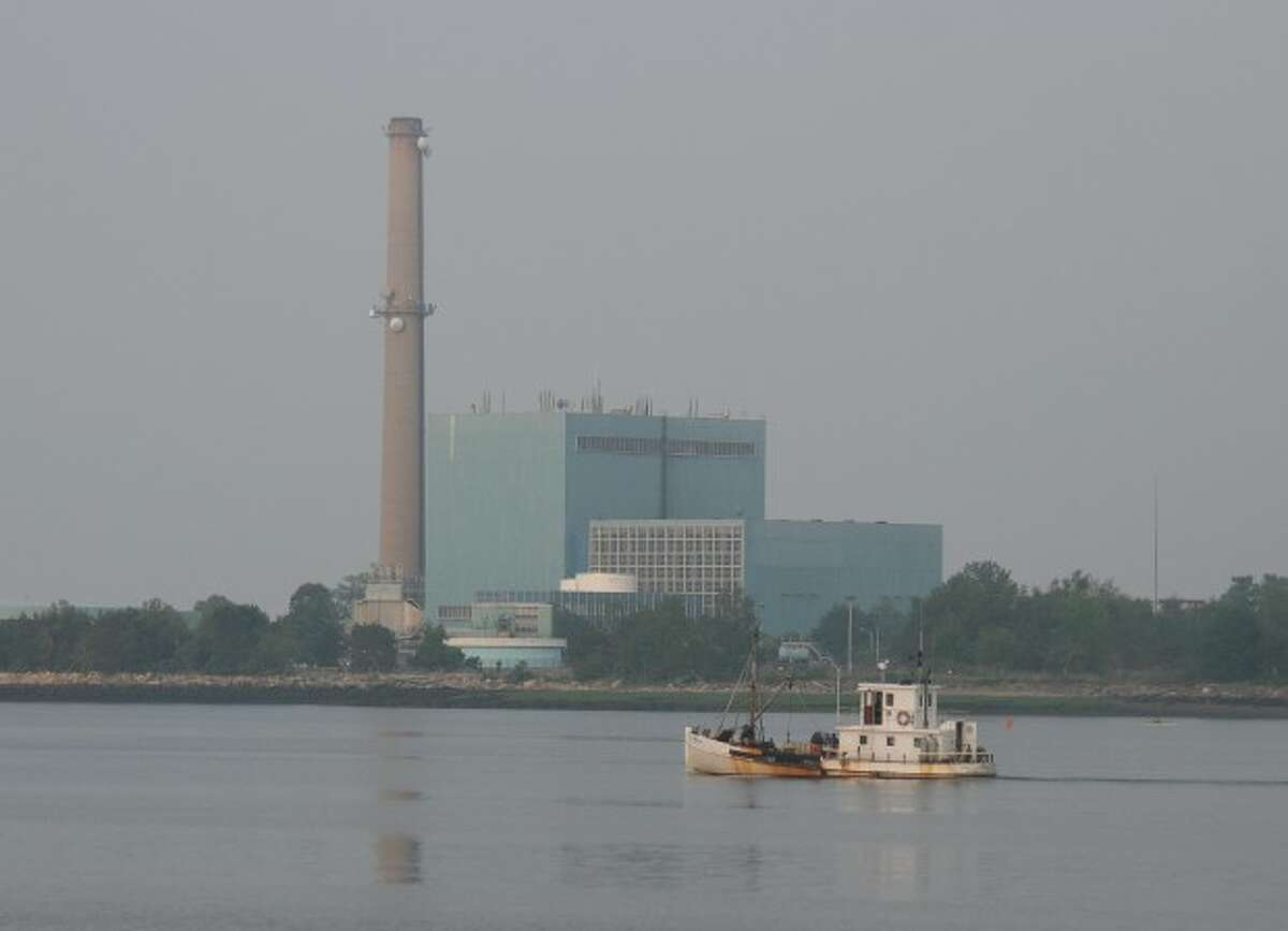 An oyster boat heads out of Norwalk Harbor as NRG's Manresa Power Plant looms in the background Wednesday morning. Photo by CHRIS BOSAK