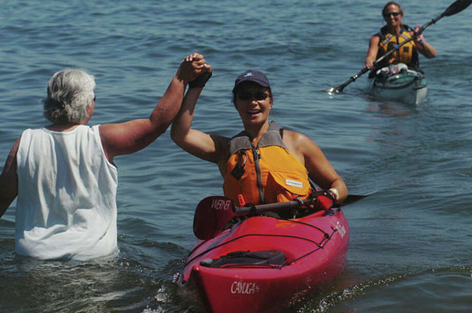 Audrey Yu of Norwalk gets congratulations from Shirleen Dubuque as she pulls into Calf Pasture Beach after conpleting the Kayak for a Cause kayak across Long Islan Sound Saturday. / (C)2011, The Hour Newspapers, all rights reserved