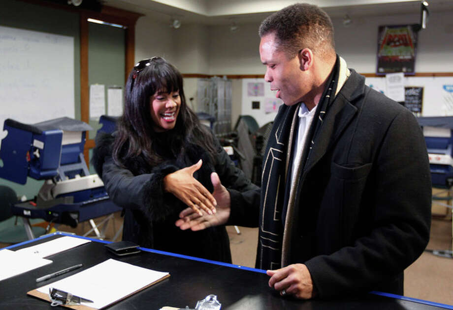 FILE - In this March 9, 2012 file photo, Rep. Jesse Jackson Jr. , D-Ill., and his wife, Chicago Alderman Sandi Jackson, ask each other for their support and votes as they arrive at a polling station for early voting in Chicago. On Friday, Feb. 15, 2013, Jackson, who resigned last year after nearly 17 years in office, was charged with spending $750,000 in campaign funds on personal expenses. His wife, Sandi, who resigned from the City Council in January 2013, was charged with filing false income tax forms. (AP Photo/M. Spencer Green, File) / AP